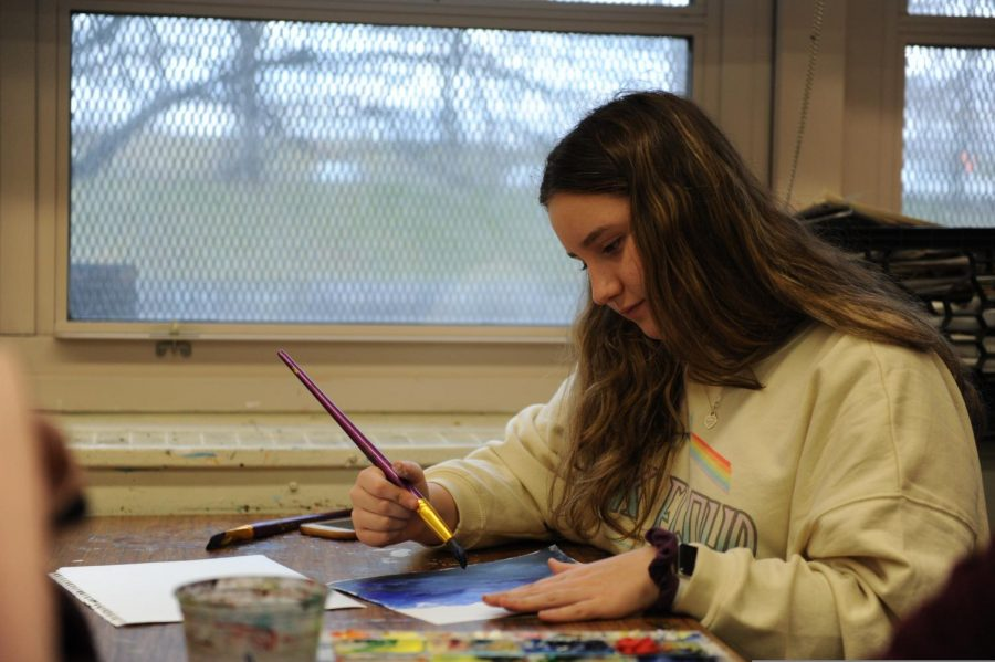 A student works on her piece in painting.