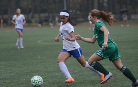 A student on the Girls' Varsity Soccer team runs to steal the ball.