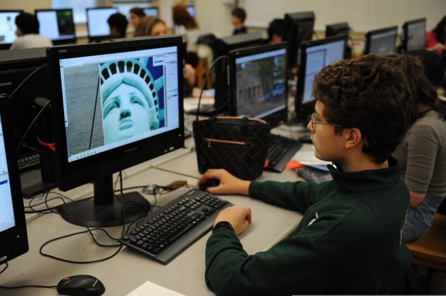 A Photography student edits his photo for his project.