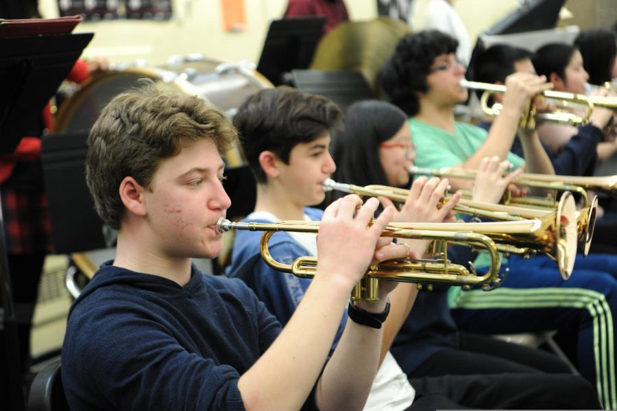 Students in Concert Band practice playing the trumpet.