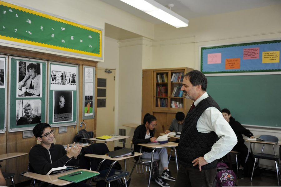 Mr. Gazzola talks to a student in an English class.