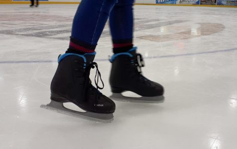 A close up of an ice skater's skates.