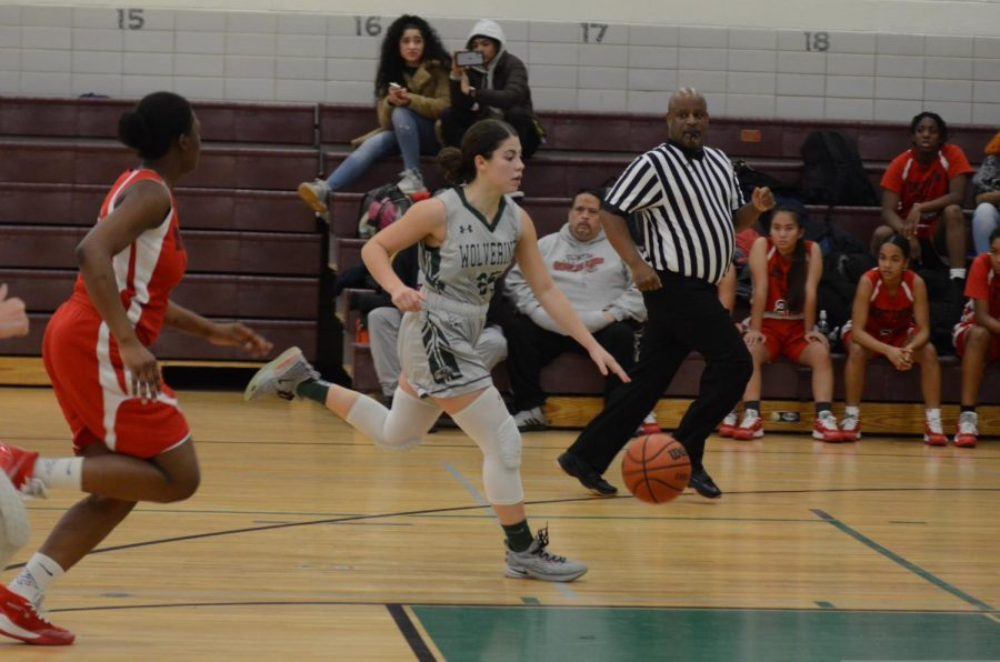 Members of the Girls' Varsity Basketball team dodge their opponents during a game.