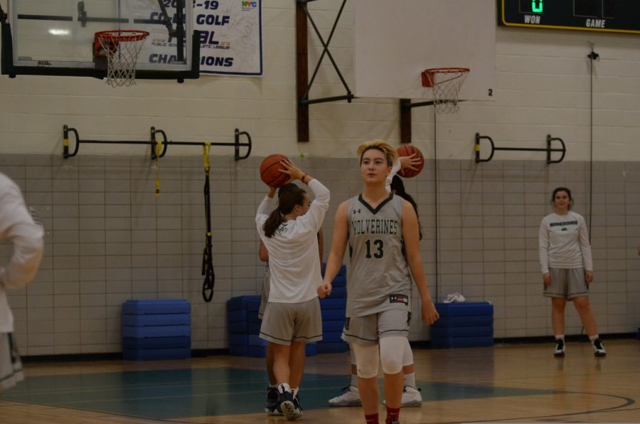 Girls varsity basketball players warm up before a game.