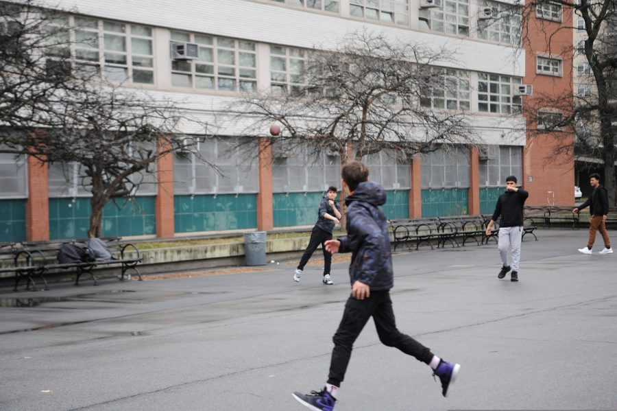 Some students play football during a rainy spring afternoon.