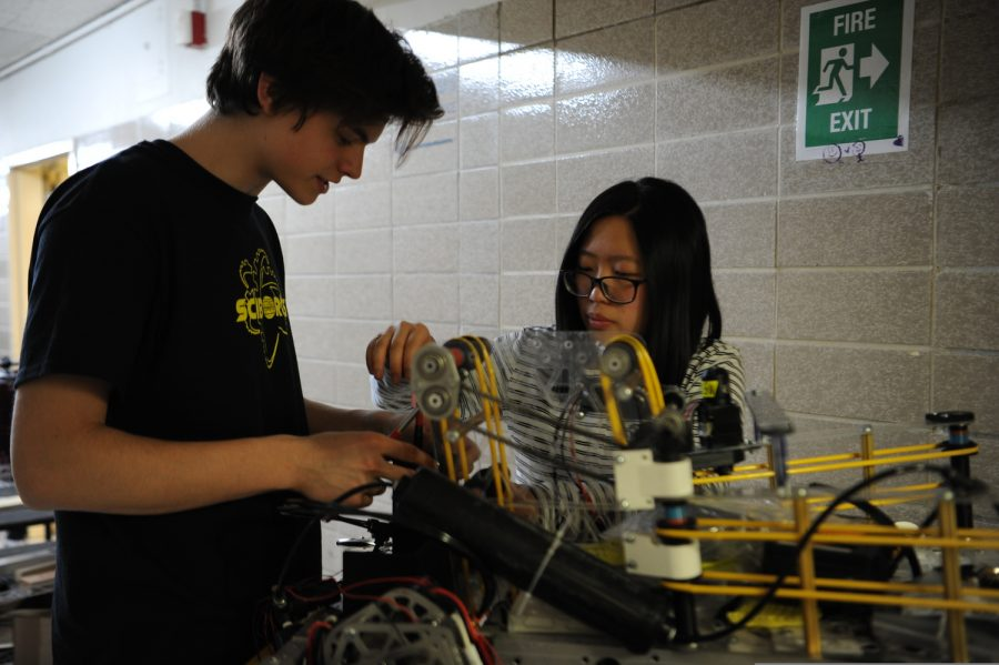 The captain of the Sciborgs, Lauren Siu '20 teaches the future captain, Xano Sweeting '21, how to work on a specific mechanism on the robot.