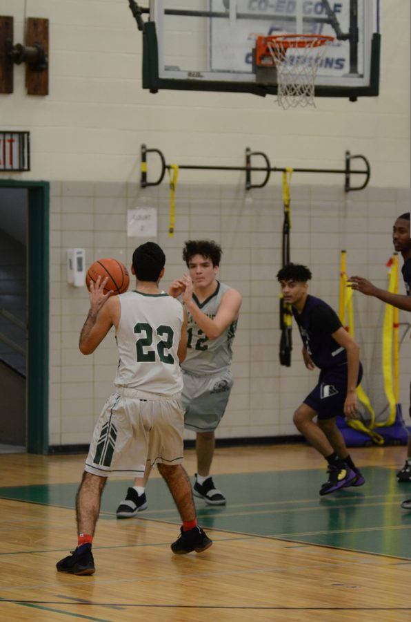 Boys basketball players set up for a play during a game.