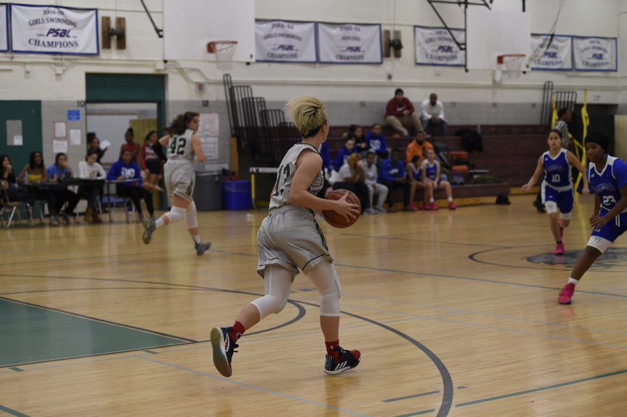 A member of the Girls' Varsity Basketball team participates in a game.