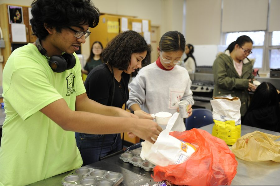Students measure out flour for their recipe.