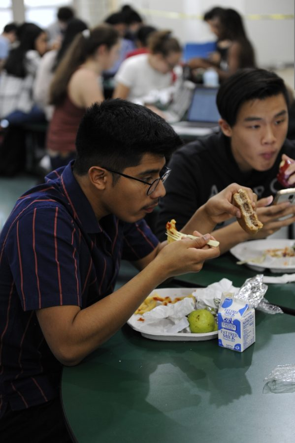 Some seniors enjoy their lunch at the green tables.