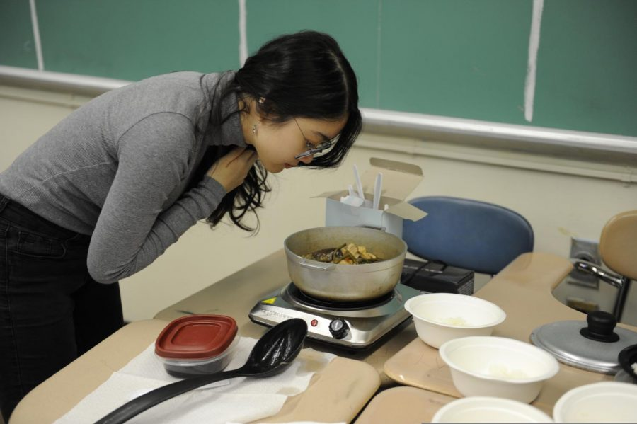 A student smells a dish being served at a meeting for Filipino Culture Club.