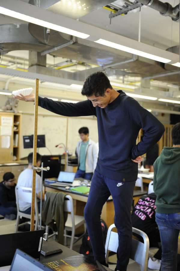 A student stands on a chair to take measurements.