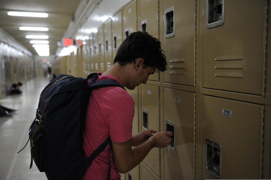 A+student+unlocks+his+locker.