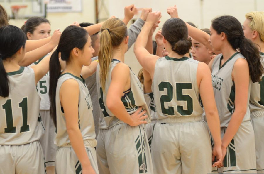 Members of the Girls' Varsity Basketball team cheer together during a time out.