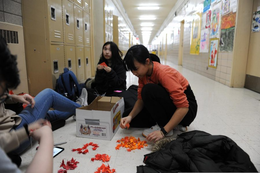 Students assemble origami cranes together in the hallway.