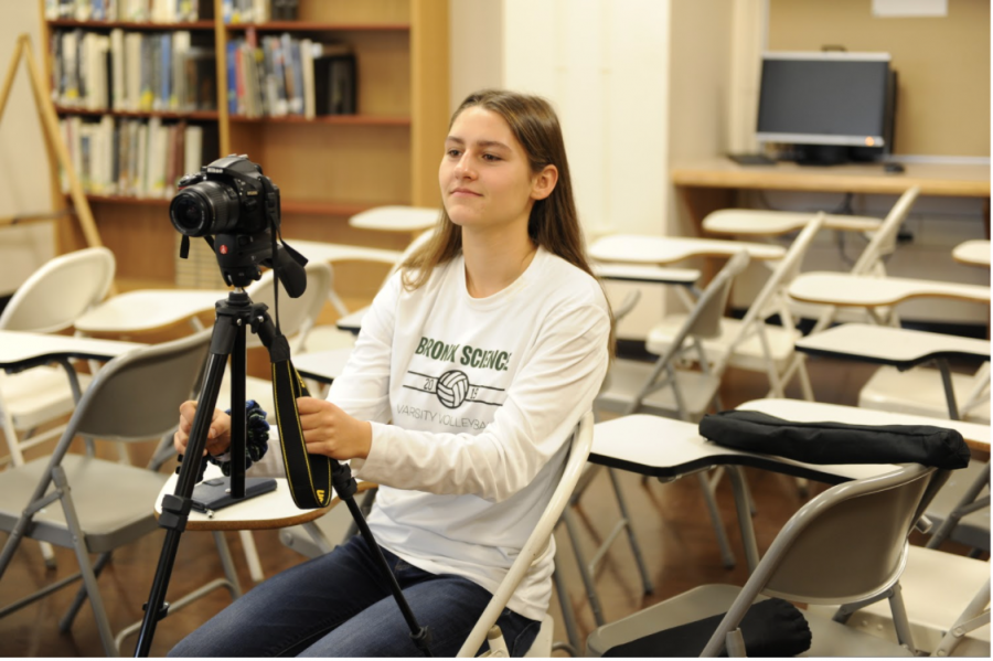"Darya Lollos smiles while participating in filming a segment for Wolverine TV while wearing her Girls' Varsity Volleyball shirt. ""I can't take myself too seriously with WTV, because it's such a lighthearted show. Sometimes, we have to be able to make fun of ourselves,"" said Lollos."