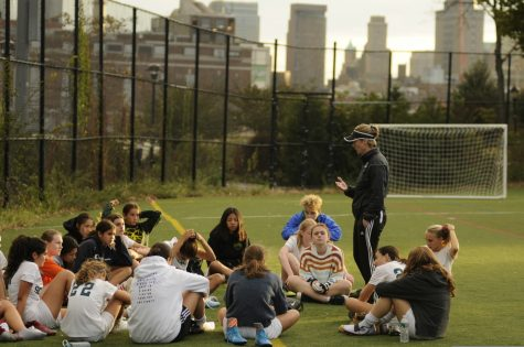 Members of the Girls' Varsity Soccer team sit together on the field during a practice. Huddles and group meetings like these are essential to the game, but with the pandemic, leagues must consider all of the potential ways to limit player contact.