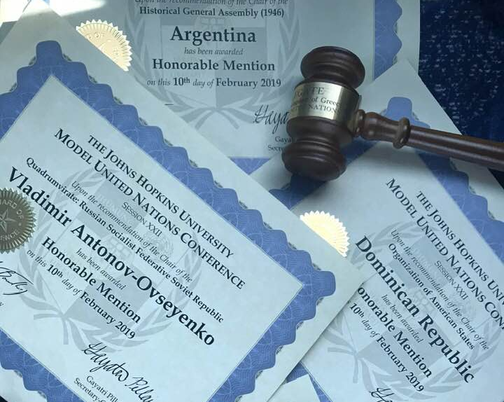 Here is a gavel along with some of the numerous awards won by the SciMUN team at John Hopkins University's recent virtual Model UN Tournament.