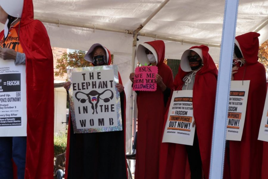 Demonstrators+in+Cleveland%2C+Ohio%2C+dress+as+Handmaids+from+Margret+Atwood%E2%80%99s+dystopian+novel+%27The+Handmaid%E2%80%99s+Tale.%27+The+clothing+from+the+novel+became+a+symbol+of+the+opposition+to+Justice+Barrett+after+it+was+claimed+that+the+patriarchal+society+of+the+novel+was+based+on+the+Catholic+organization+People+of+Praise%2C+to+which+Barrett+belonged.+This+claim+has+since+been+repudiated%2C+but+the+symbolism+has+remained.