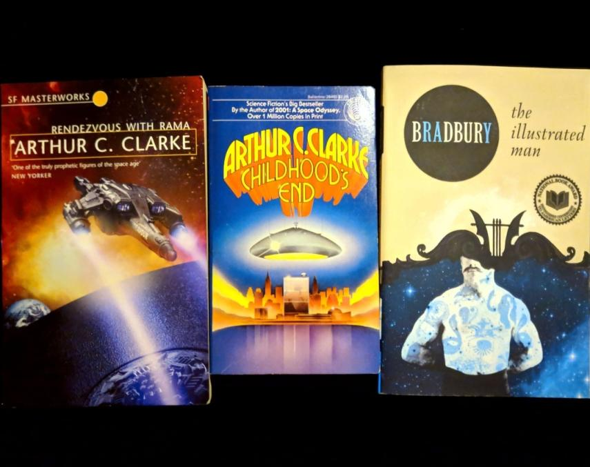 From left to right, three of my favorite science fiction books that I own are 'Rendezvous with Rama' and 'Childhood's End' by Arthur C. Clarke, and 'The Illustrated Man' by Ray Bradbury, which is a collection of his short stories.