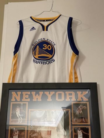 Pictured are two pieces of signed NBA apparel, sold exclusively through the NBA Store, a Stephen Curry Jersey and a Frank Ntilikina Signed Board.