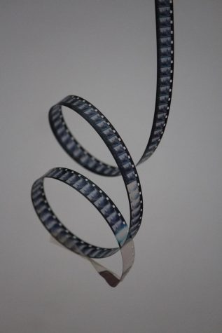 Here is an old 8 mm film reel on a white background. Due to the Coronavirus pandemic, movies can only be watched safely at home right now.