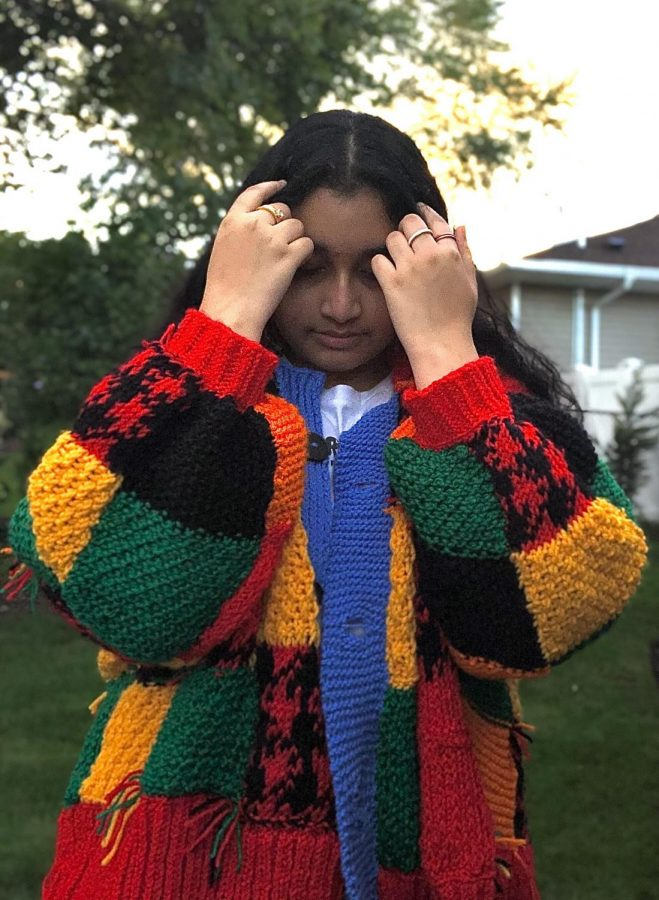 Shaira Jafar '21 shows off the multiple different stitches needed to create the cardigan.