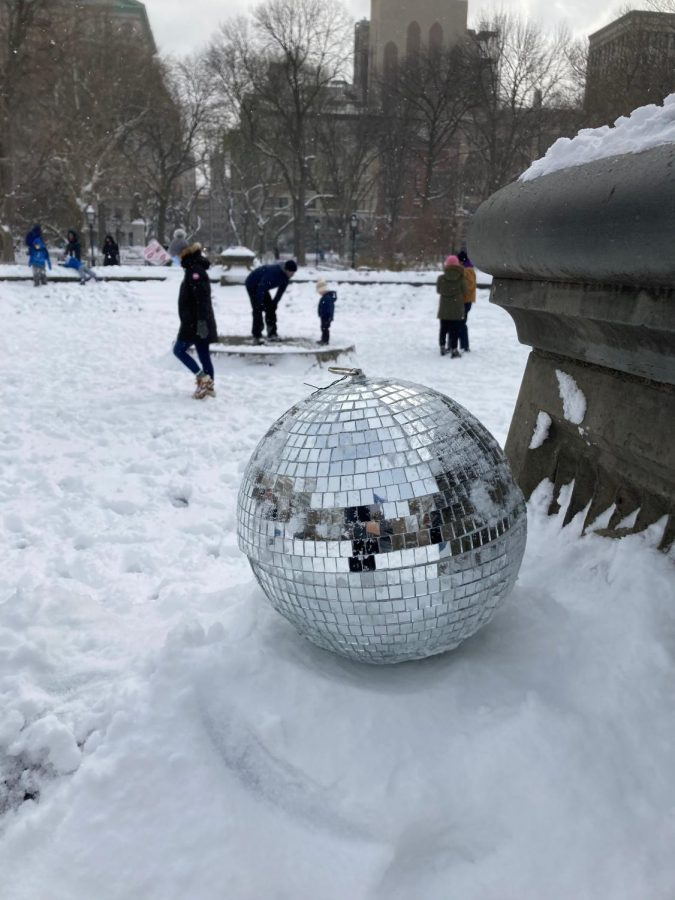 A disco ball in Washington Square Park reflects the fun that New Yorkers of all ages are having in the snow.