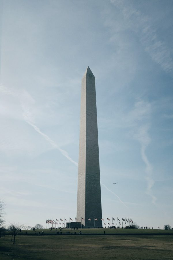 The Washington monument, an iconic symbol of the capitol, stands surrounded by flags and visitors in the morning.