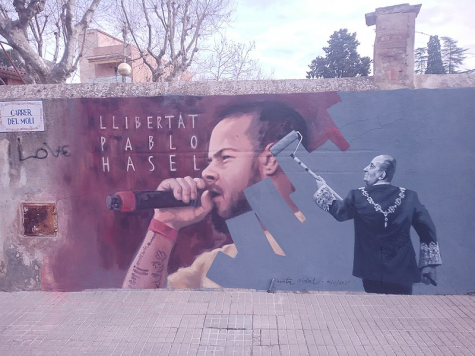"A mural in Spain depicts a portrait of Pablo Hasél being painted over by former King Juan Carlos. The mural symbolizes the censoring of Hasél by the monarchy and a wish for his freedom. The text reads ""Free Pablo Hasél."""