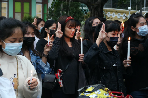 Protestors hold up the three-finger salute, which originated in the