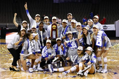 The University of Kentucky's Volleyball team poses with the fruits of their victory -  swag gear, banners, confetti, and pieces of the volleyball net - in the NCAA tournament, after they defeated the Texas Longhorns to take home their first ever NCAA Championship title.